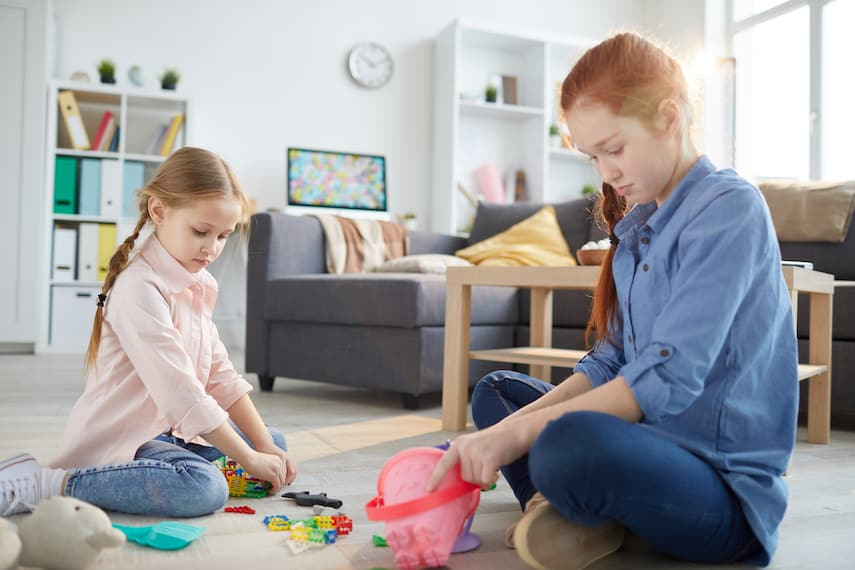 redheaded teenager playing with younger girl in living room