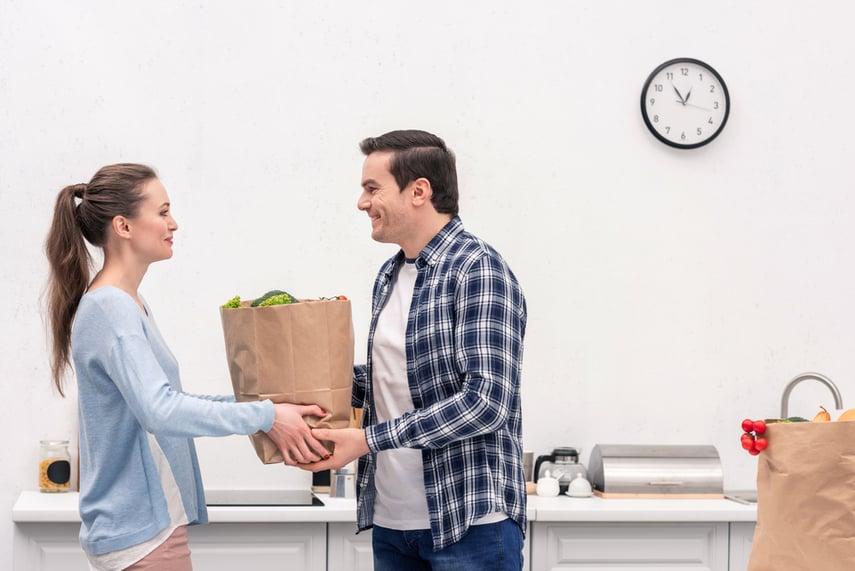 woman handing bag of food to man