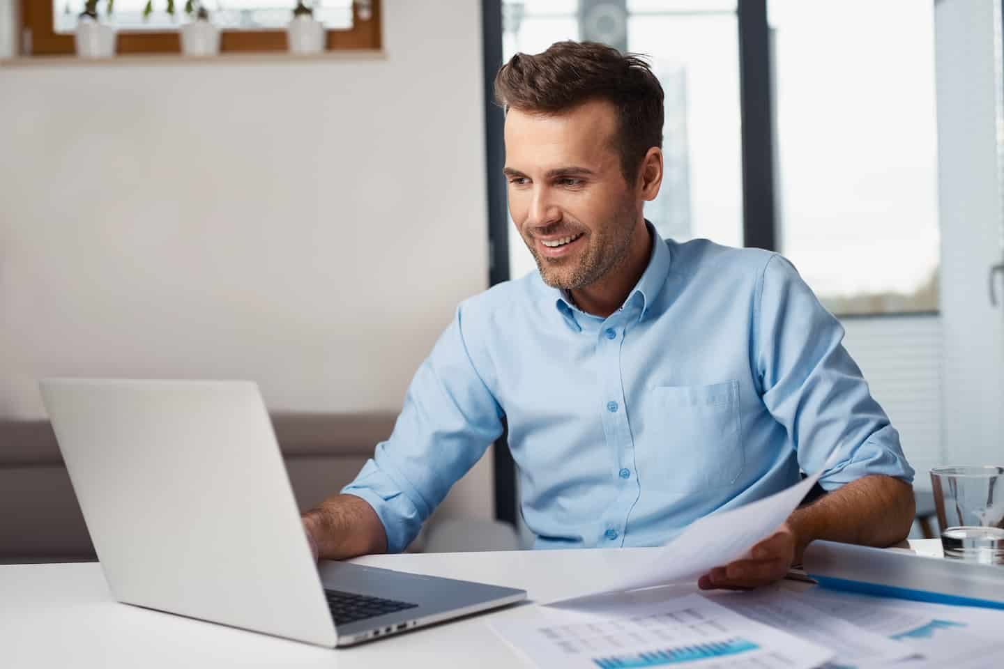 man holding bank statement in front of laptop