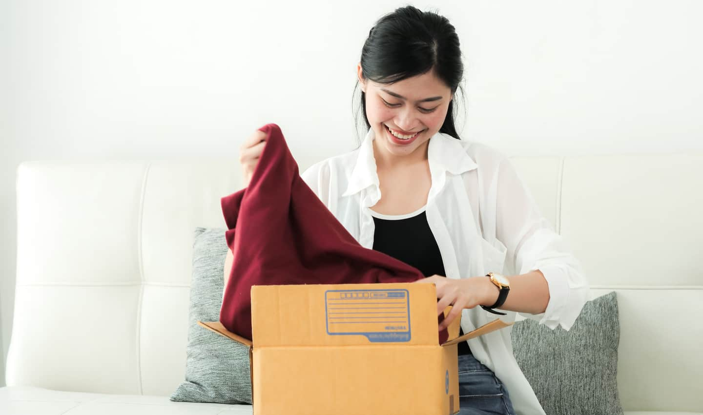 woman putting clothes in a box