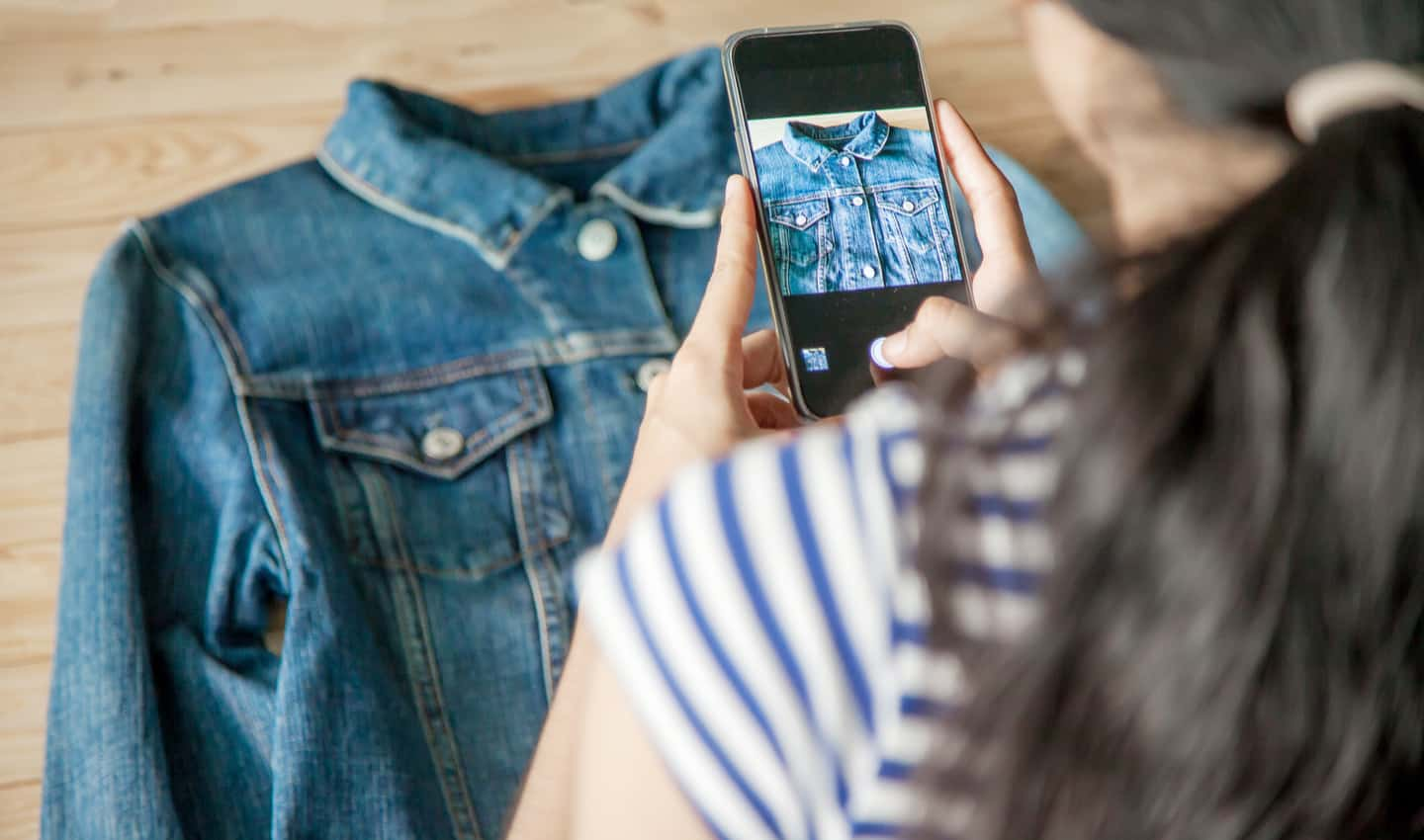 woman taking pictures of a jacket to sell on Craigslist