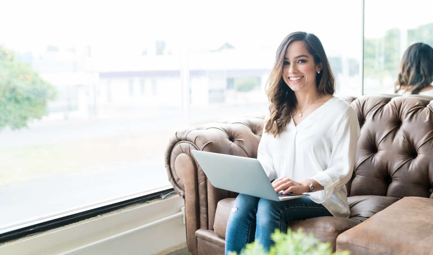 woman sitting on loveseat with laptop