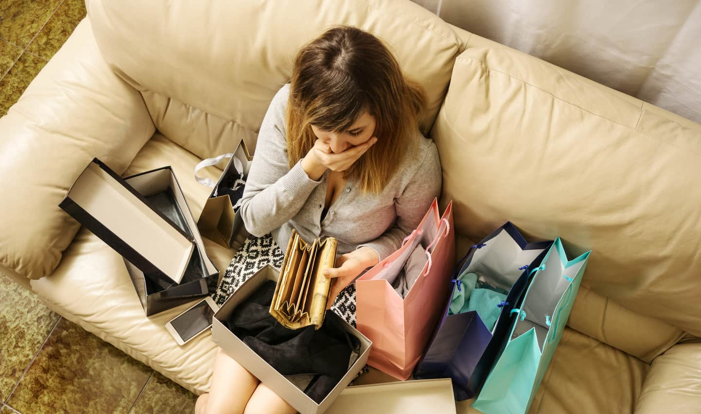 woman sitting on couch with shopping bags looking at her empty wallet
