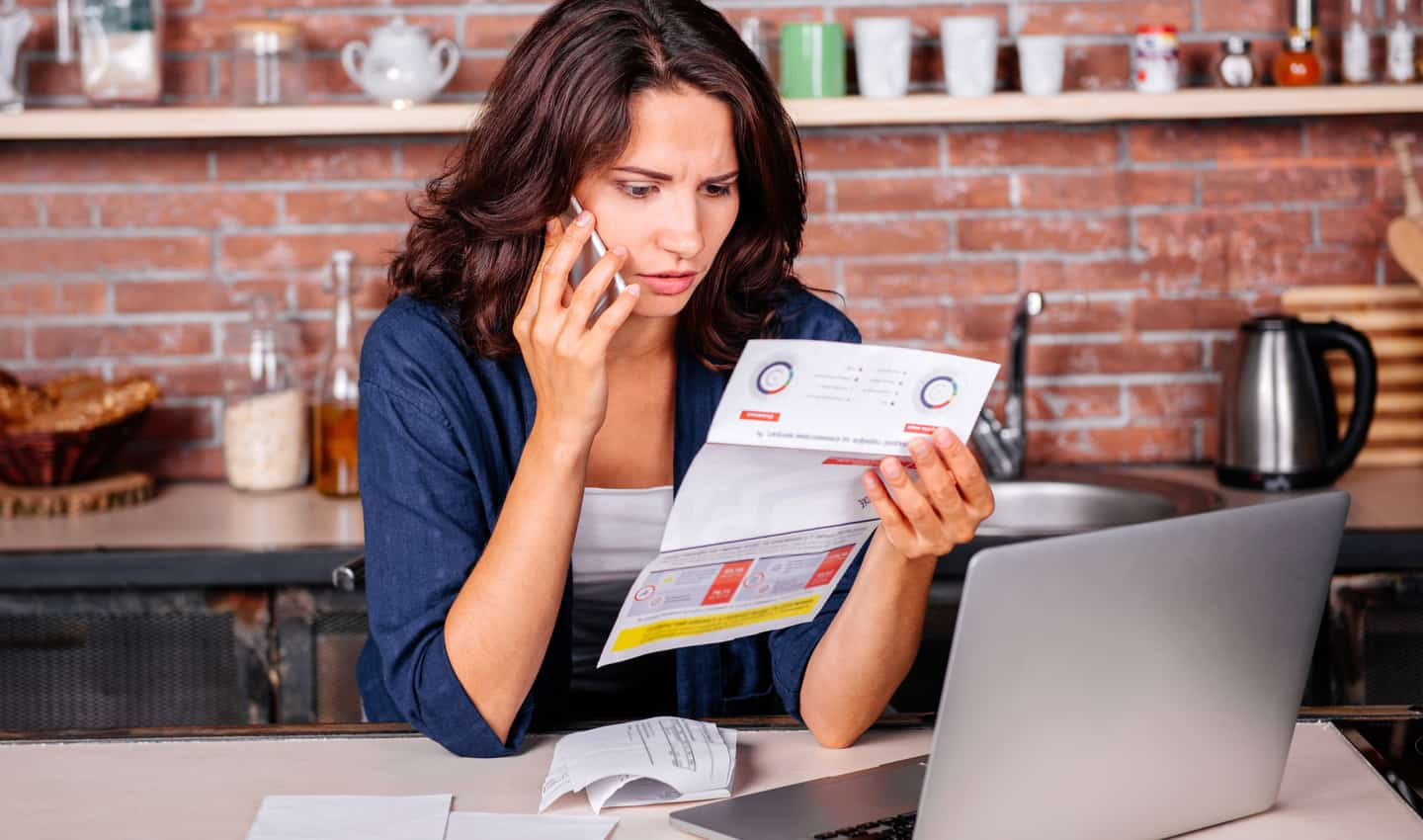 woman on the phone looking at paper bill