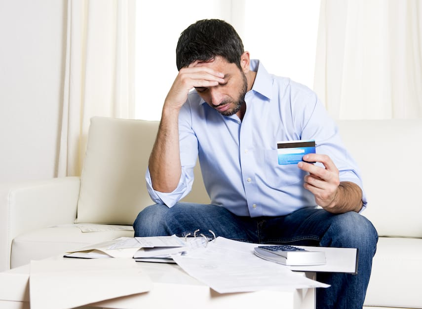 young latin american man sitting on sofa with credit card bills looking worried and stressed