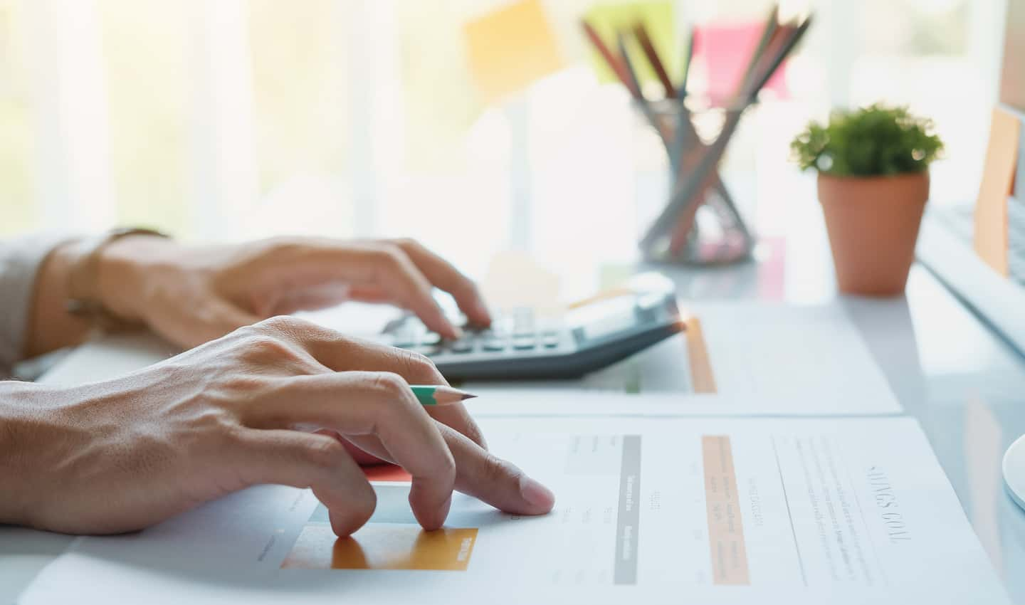 woman's hands calculating business expenses
