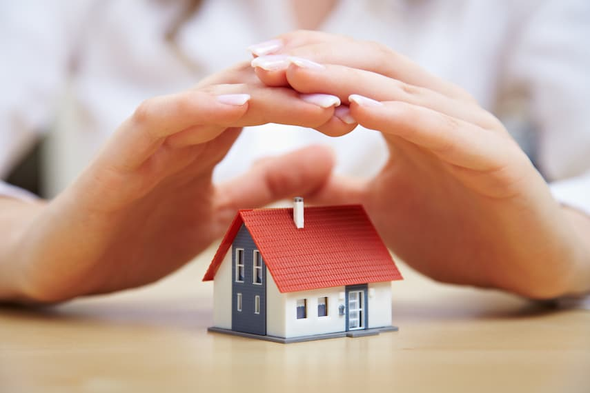 woman holding her hands over a small model house