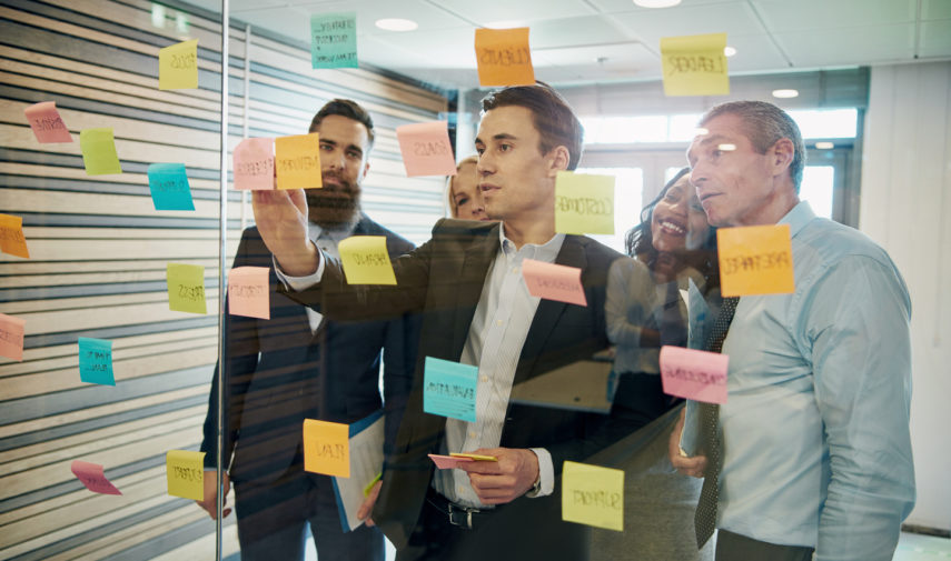 man creatively solving problems with sticky notes