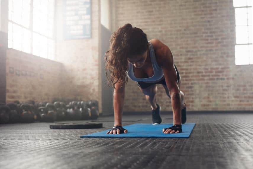 athletic woman doing push ups on workout mat