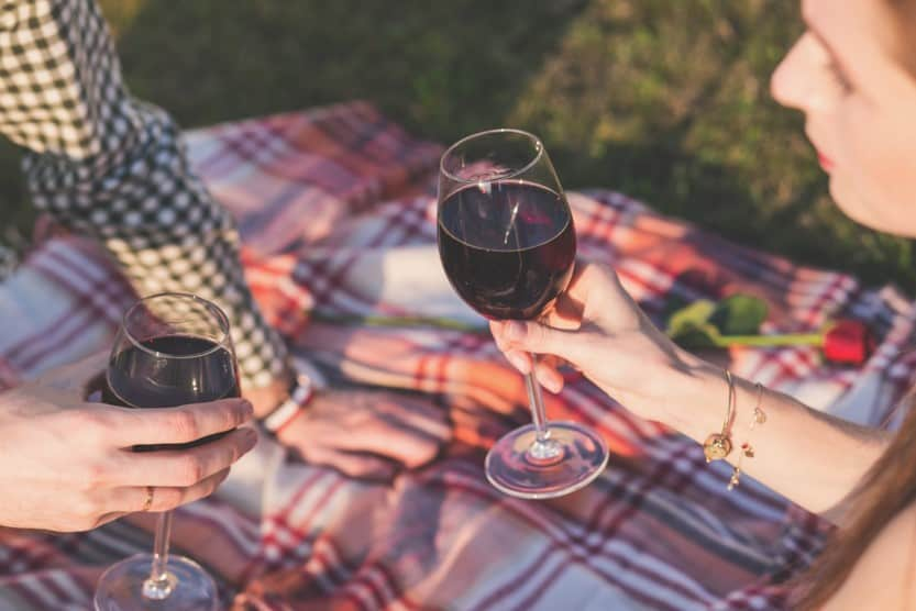 couple drinking wine while having a picnic